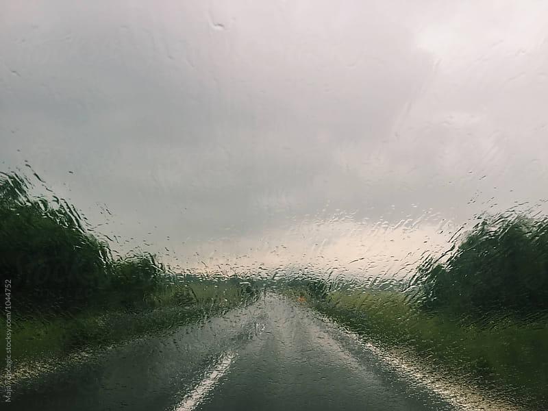 Empty road through a rainy window by Maja Topcagic for Stocksy United
