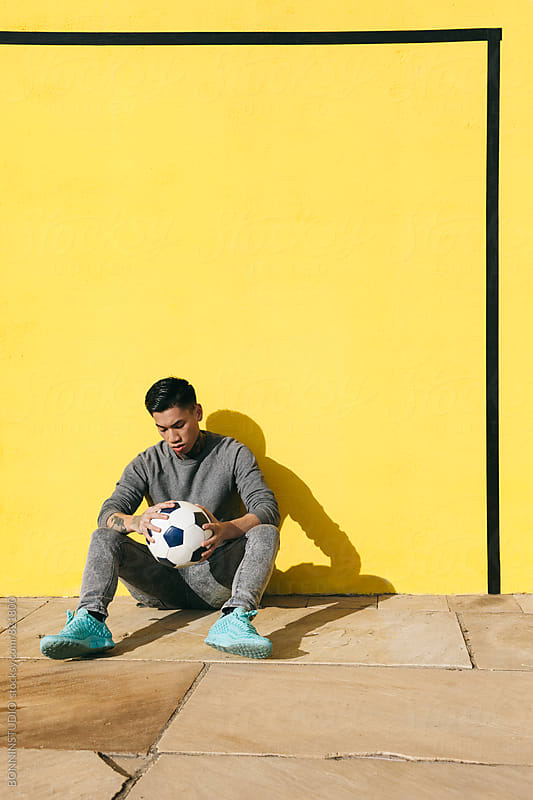 Asian tattooed man sitting with soccer ball in front of a yellow wall. by BONNINSTUDIO for Stocksy United