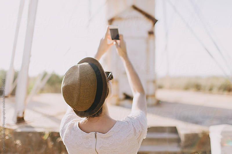Girl taking photos with cell phone by Dylan M Howell Photography for Stocksy United