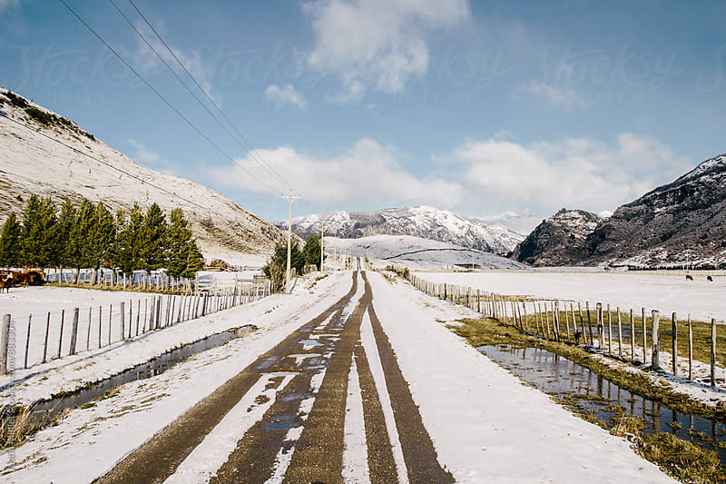 Tire tracks on a snow covered road in rugged country by Justin Mullet for Stocksy United