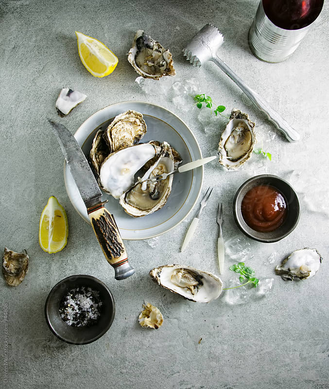 Oysters and condiments on a table. Seen from overhead. by Darren Muir for Stocksy United