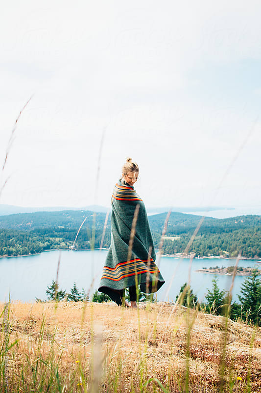 Young Blonde Woman Wrapped In Wool Blanket Twirling On Forest Island Hillside by Luke Mattson for Stocksy United
