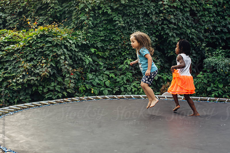 Caucasian and black girl jumping together on a trampoline by Gabriel (Gabi) Bucataru for Stocksy United