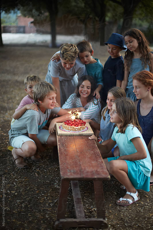Group of kids celebrating a birthday party by Miquel Llonch for Stocksy United