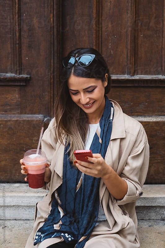 Pretty Woman Typing on the Phone while Having Smoothie  by Katarina Radovic for Stocksy United