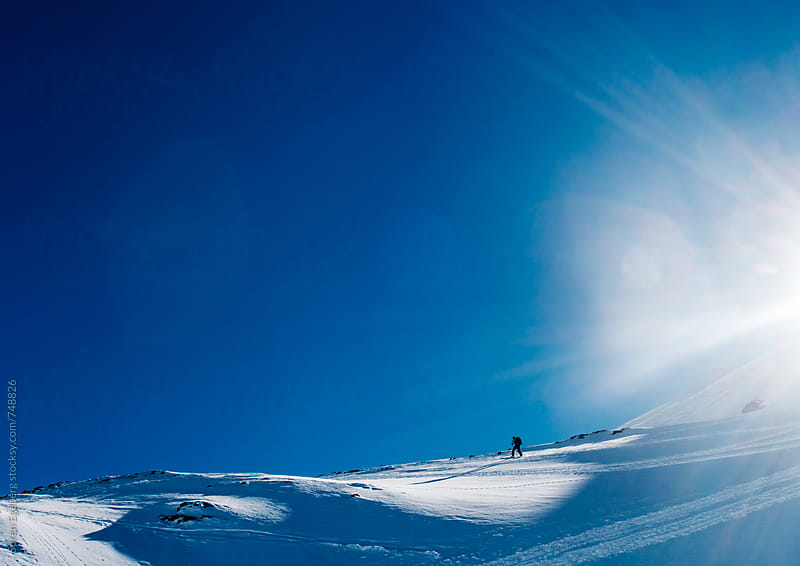 Skier climbing up a mountain in winter snow by Søren Egeberg Photography for Stocksy United