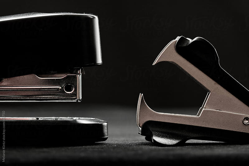 Stapler and staple remover  opposite to one another before black background by Melanie Kintz for Stocksy United