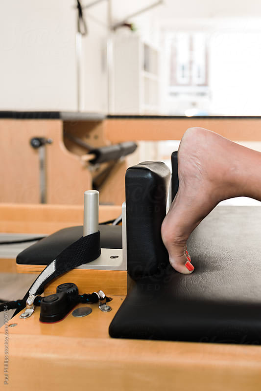 Woman's foot pressed against stop on a reformer. Pilates exercise. by Paul Phillips for Stocksy United