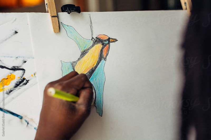 Hand of a black girl drawing a bird by Gabriel (Gabi) Bucataru for Stocksy United