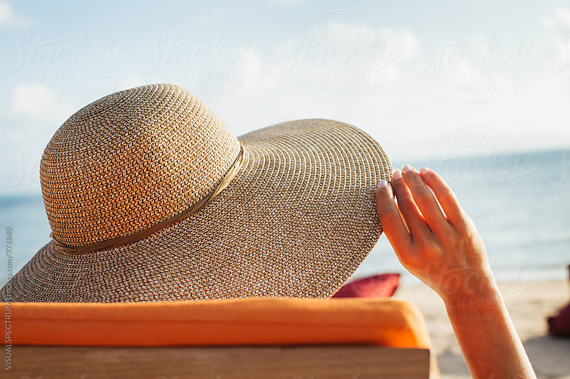 Close Up of Woman With Large Straw Hat Tanning on Sunbed by Julien L. Balmer for Stocksy United