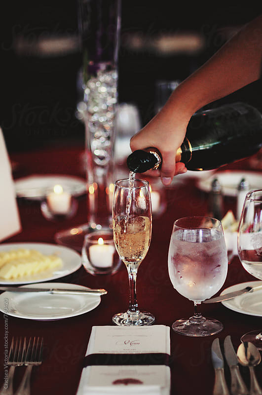 Champagne being poured at a wedding by Chelsea Victoria for Stocksy United
