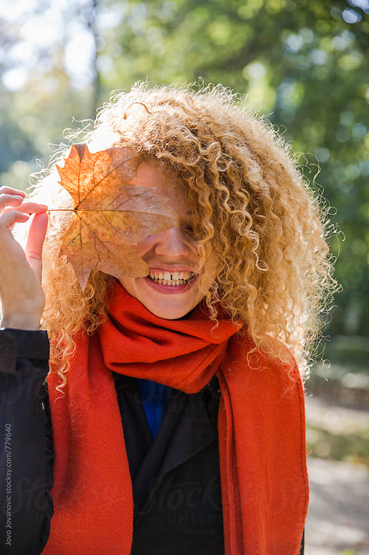 Beautiful young woman holding a maple leaf. Autumn portrait. by Jovo Jovanovic for Stocksy United