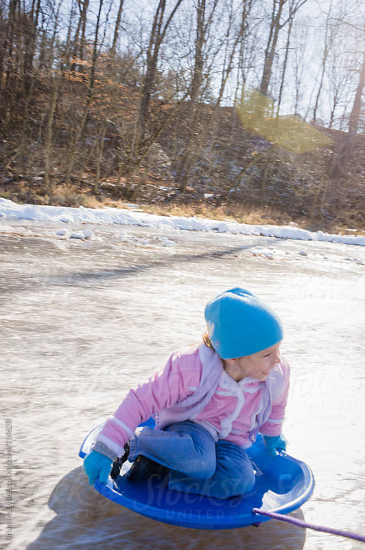 Happy Little Girl Sledding on Frozen Pond by Brian McEntire for Stocksy United