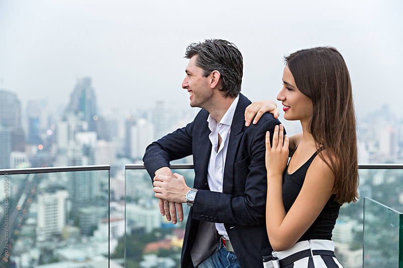Handsome young couple enjoying the view of a busy metropolis  by Jovo Jovanovic for Stocksy United