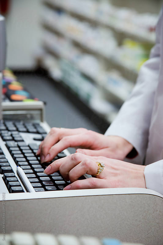 Pharmacy: Pharmacist Typing In Medicine Order by Sean Locke for Stocksy United