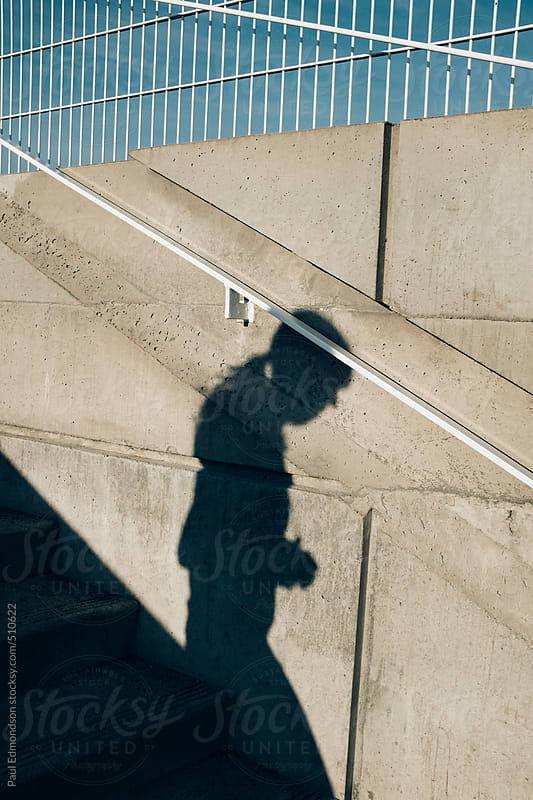 Shadow of woman walking down concrete stairway by Paul Edmondson for Stocksy United
