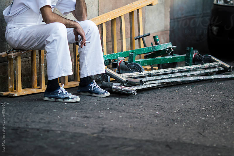 worker in white uniform sits on a ladder on the street and smokes a cigarette by Igor Madjinca for Stocksy United