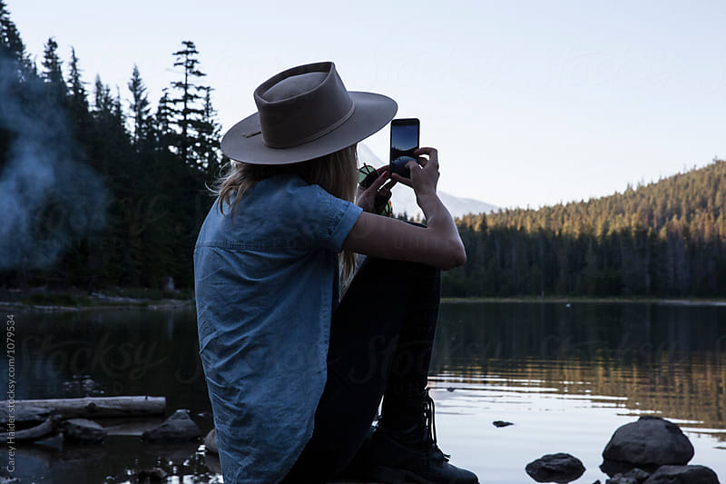 Woman Taking A Photo Of A Lake With Her Cell Phone by Carey Haider for Stocksy United