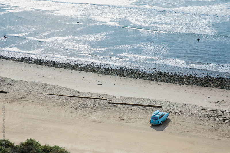 Car with surfboard parked on the sand at the beach by Curtis Kim for Stocksy United