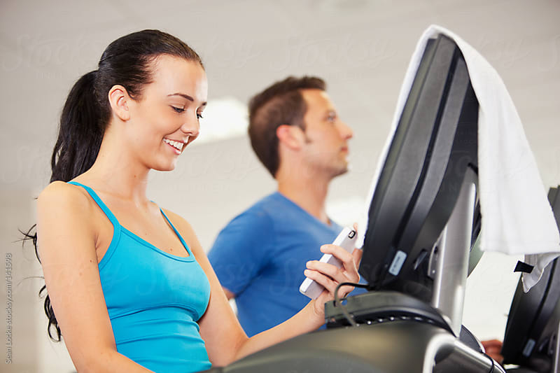 Gym: Woman Checks Email While Walking on Treadmill by Sean Locke for Stocksy United