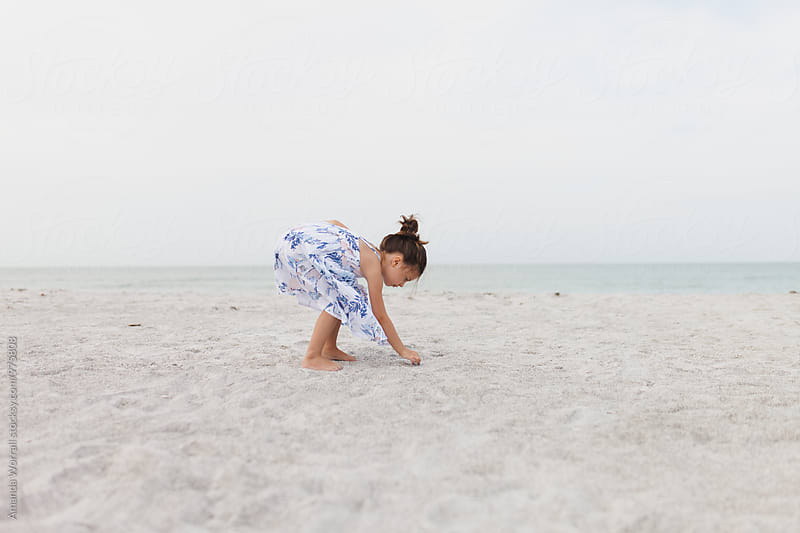 Young girl picking up a shell on the beach by Amanda Worrall for Stocksy United