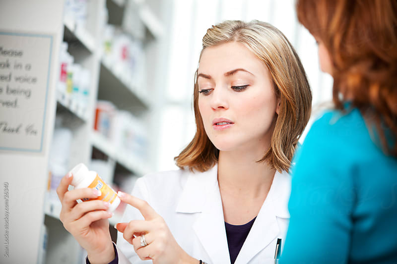 Pharmacy: Assisting Customer with Medicine Label by Sean Locke for Stocksy United