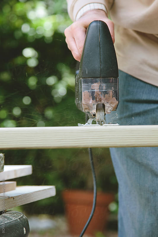 Man with electric saw cutting wood. by BONNINSTUDIO for Stocksy United