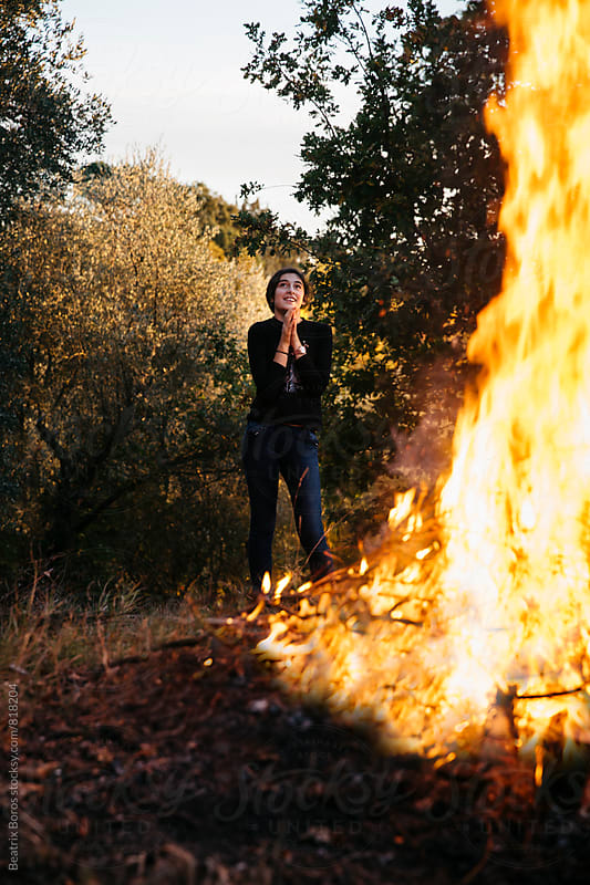 Pre-teenager girl passionately watching a big fire by Beatrix Boros for Stocksy United
