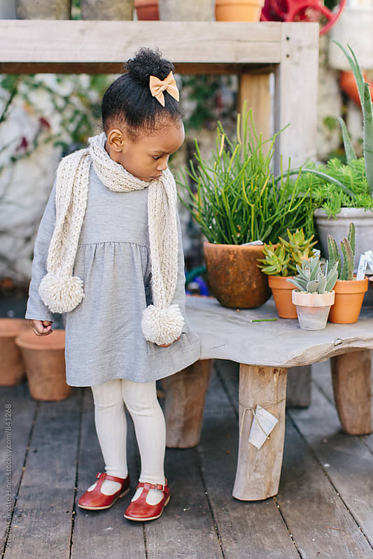 A little girl standing by a stool in a garden / flower market.  by Kristen Curette Hines for Stocksy United