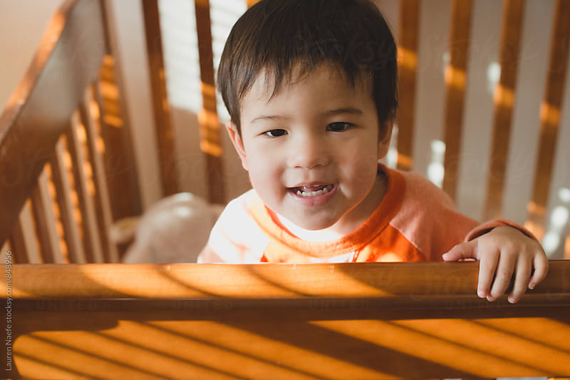 Happy toddler in crib by Lauren Naefe for Stocksy United