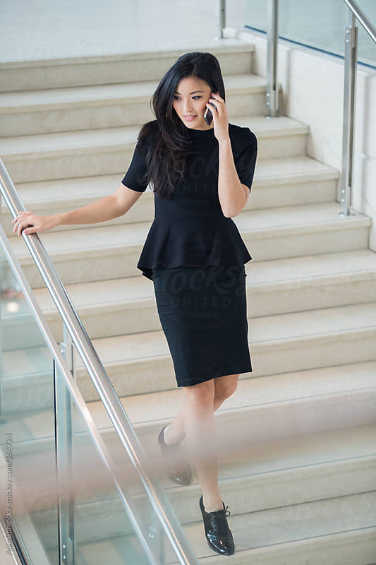 Asian businesswoman walking down the stairs talking on her cell phone by Ania Boniecka for Stocksy United