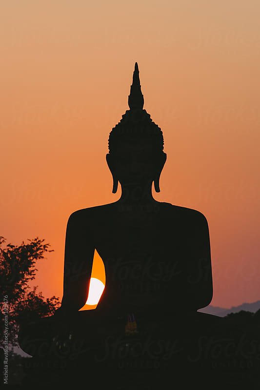 Silhouette of Buddha statue at sunset by michela ravasio for Stocksy United