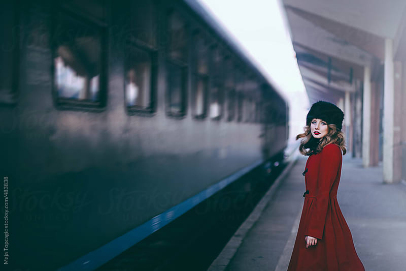 Young beautiful woman curly hair in a red coat and russian fur hat on a train station by Maja Topcagic for Stocksy United
