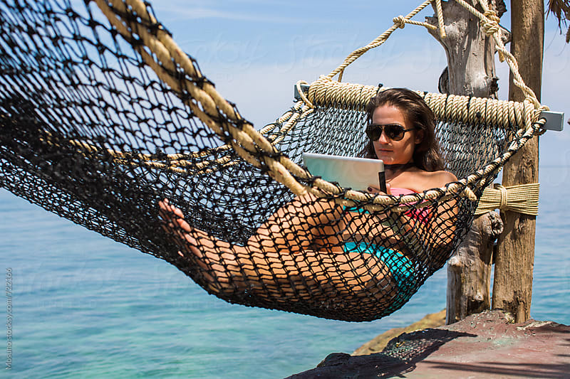 Woman Using Technology in the Hammock by Mosuno for Stocksy United