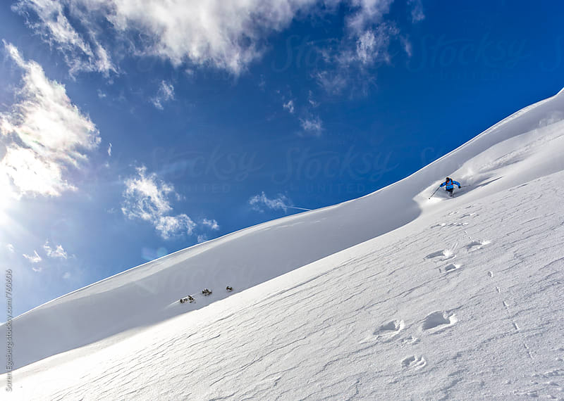 Male skier freeriding steep powder slope in the mountains of Austria by Soren Egeberg for Stocksy United