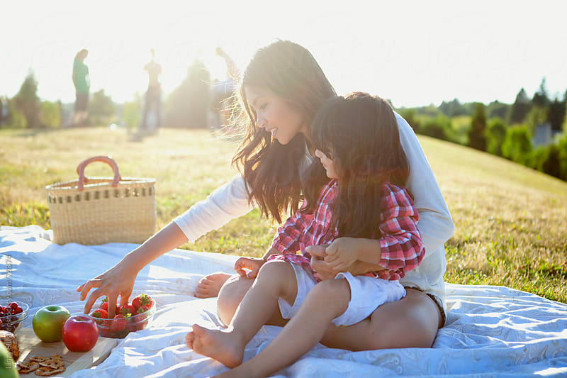 Mother and daughter grabbing fruit at summer picnic by Linzy Slusher for Stocksy United