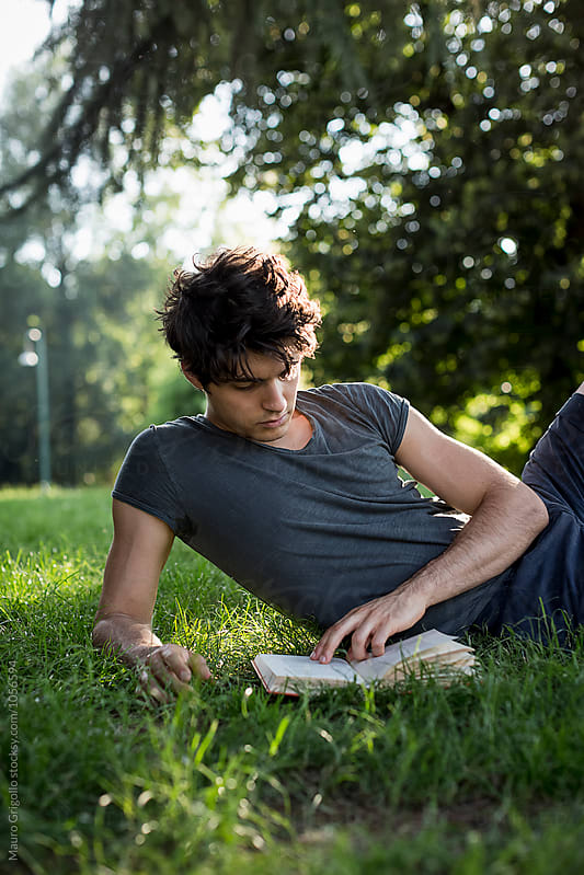 Man reading a book at the park by Mauro Grigollo for Stocksy United