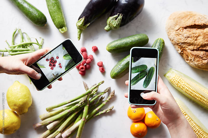 Two hands taking shots of cucumbers and raspberries using phones by Martí Sans for Stocksy United