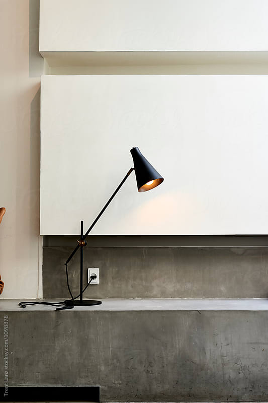 Black metal table lamp on grey surface by Trent Lanz for Stocksy United