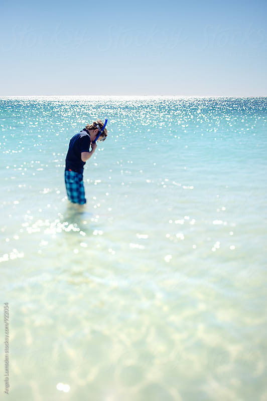 Boy standing in clear water with snorkel set and board shorts on a clear summer day by Angela Lumsden for Stocksy United