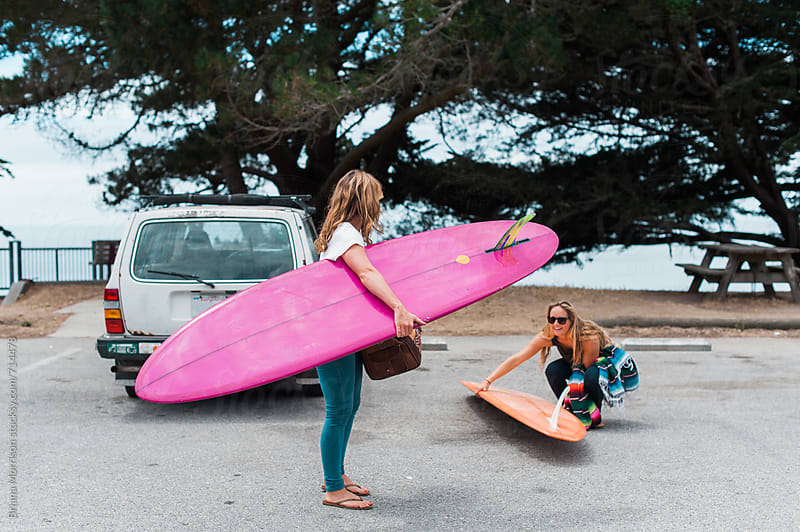 Two Young Woman Carrying Surf Boards Away from their Car by Briana Morrison for Stocksy United