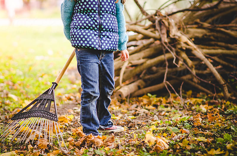 Child standing in yard with a rake