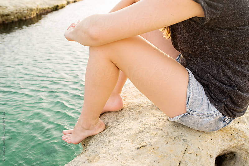 Woman sitting on rock next to ocean by Aila Images for Stocksy United