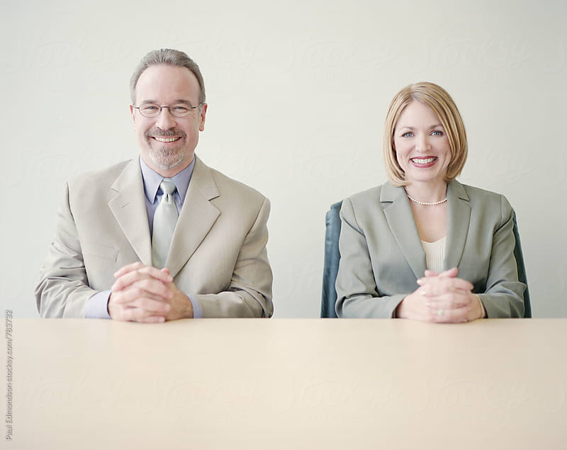 Portrait of two happy business executives sitting at desk by Paul Edmondson for Stocksy United