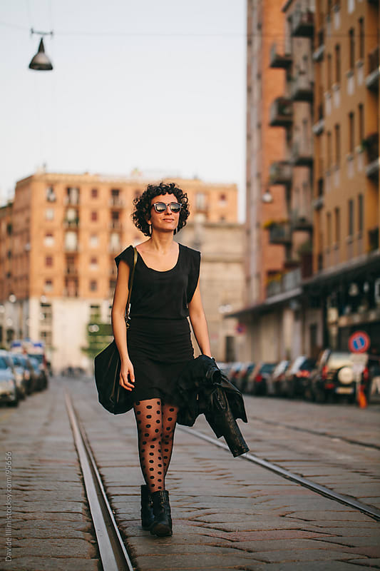Young woman walking in the street by Davide Illini for Stocksy United
