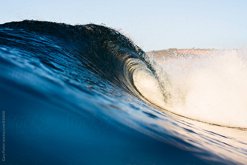 A blue and gold wave breaks and forms a small hollow barrel by Gary Parker for Stocksy United