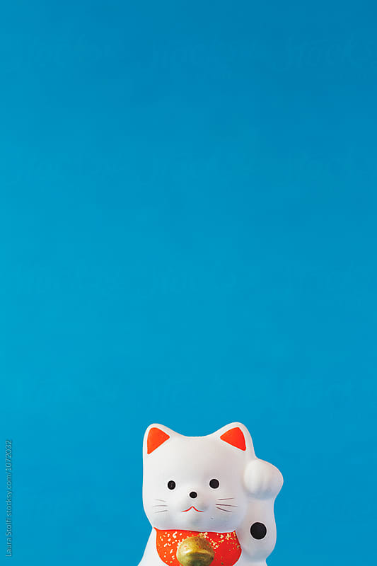 Japan's Beckoning Cat called Maneki neko reproduction on blue background by Laura Stolfi for Stocksy United