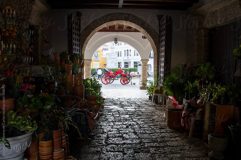 Doorway with horse carriage on background. Cartagena de Indias, Colombia travel by Alejandro Moreno de Carlos for Stocksy United