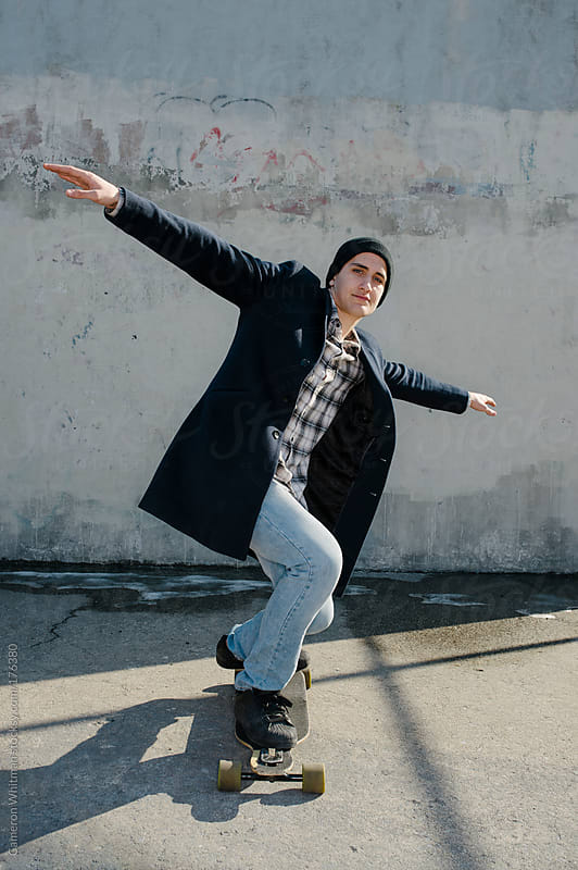 Latino American man posing on his skateboard  by Cameron Whitman for Stocksy United