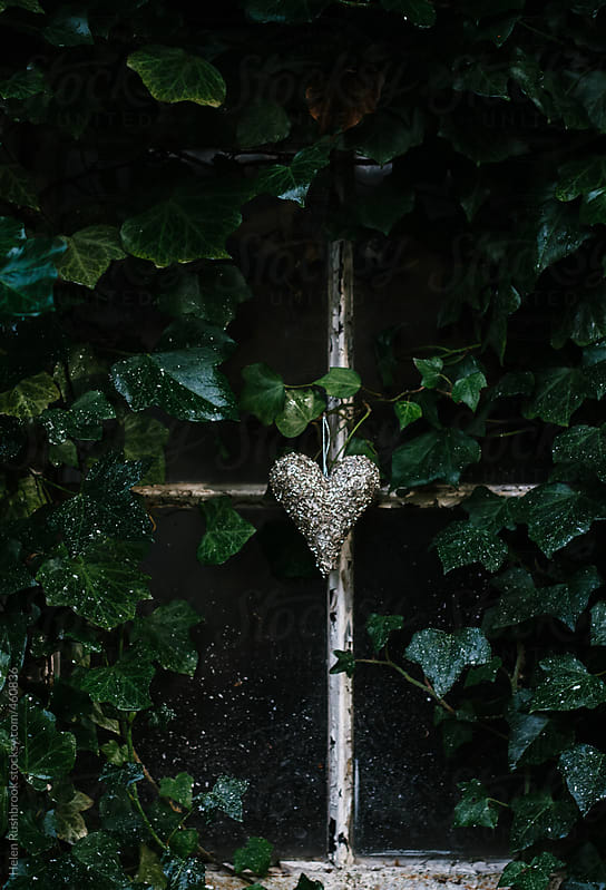 A beaded silver heart hanging in front of an ivy-clad window. by Helen Rushbrook for Stocksy United